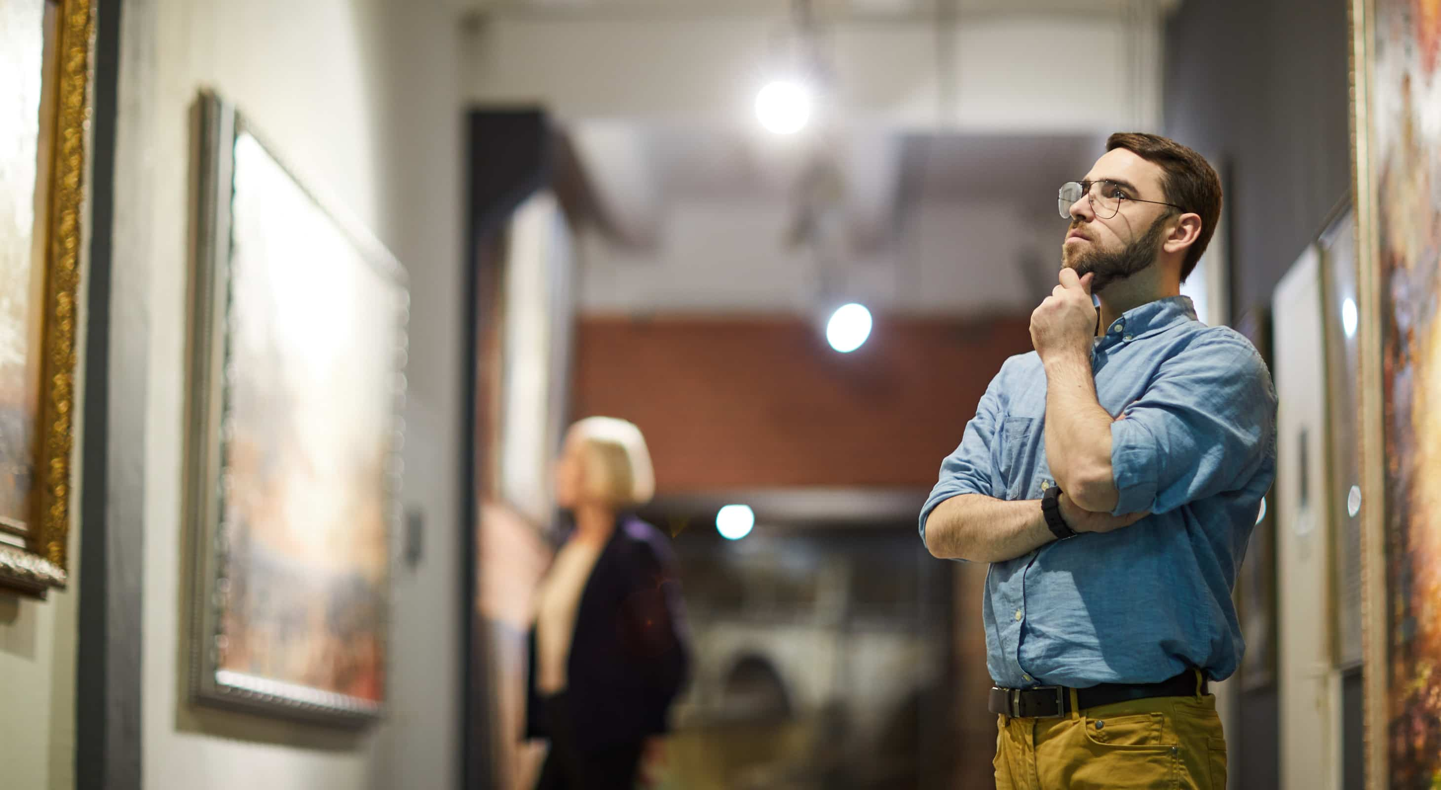 A man with a beard looking at a painting in a museum