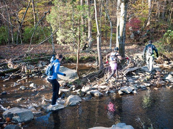 photo of hikers crossing stream in the Rivanna Trail, America's Best-Disguised Hiking Trail