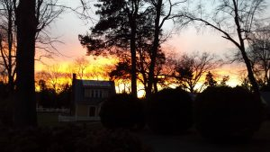 photo of setting sun behind cottages - stay at a bed-&-breakfast