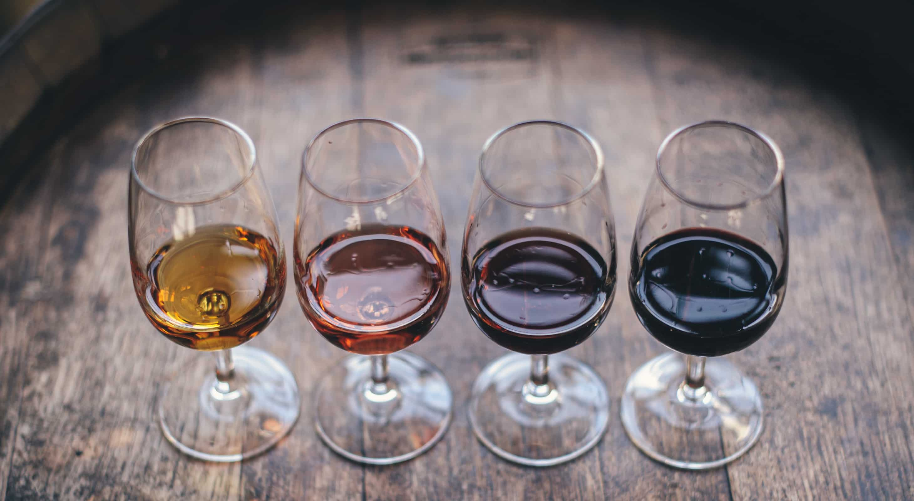 Four glasses of wine on a barrel