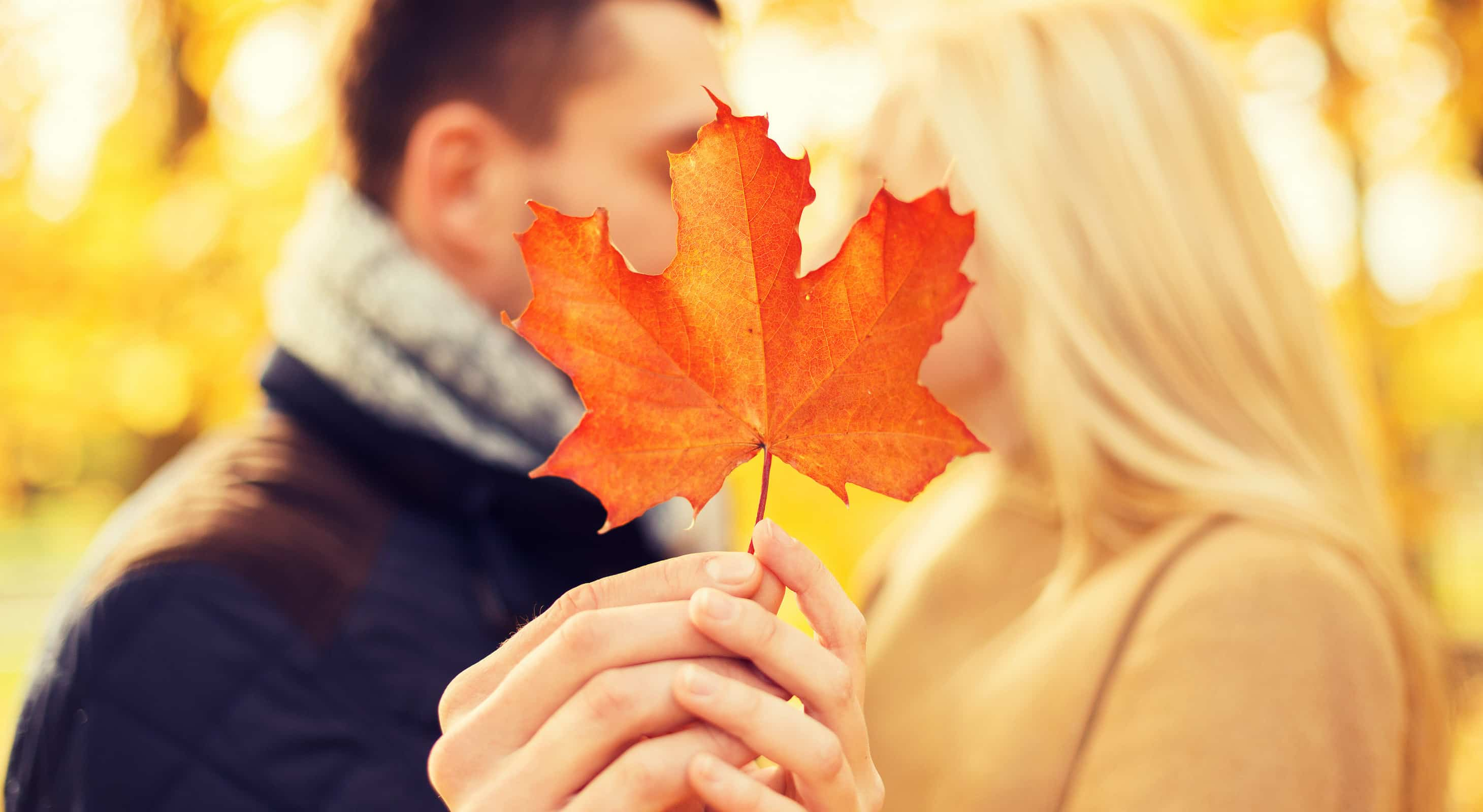 A couple holding a orange leaf in fall