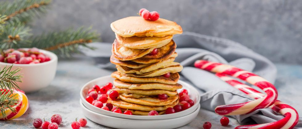 Stack of pancakes on a plate with berries next to two candy canes