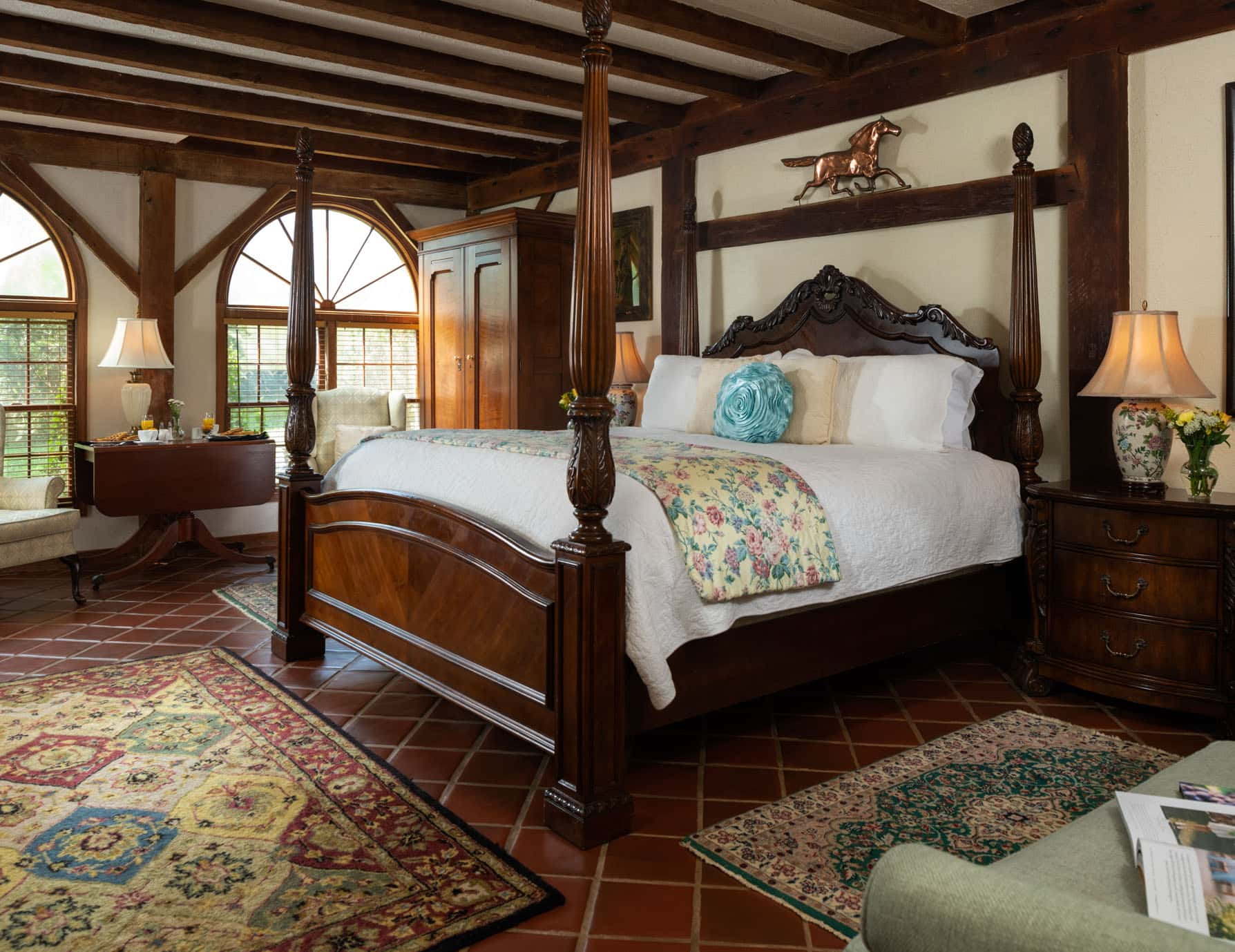 Four poster king bed in a large spacious room with ample natural light