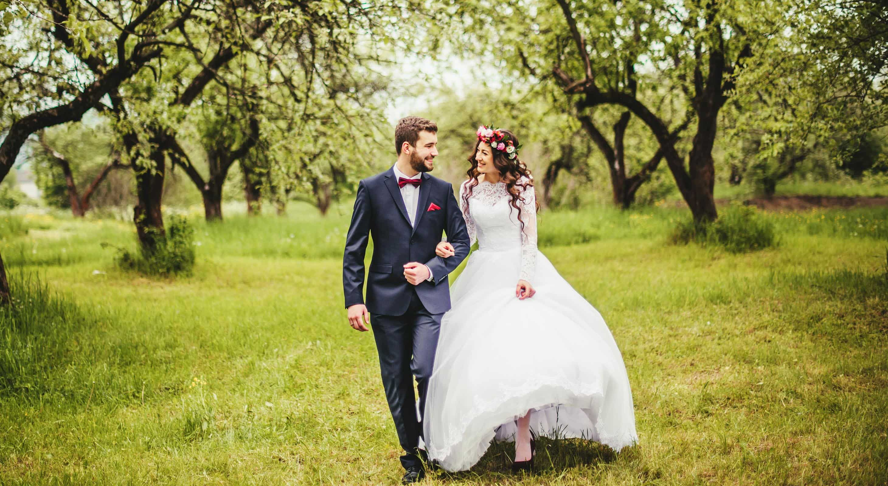 Bride and groom walking in an orchard