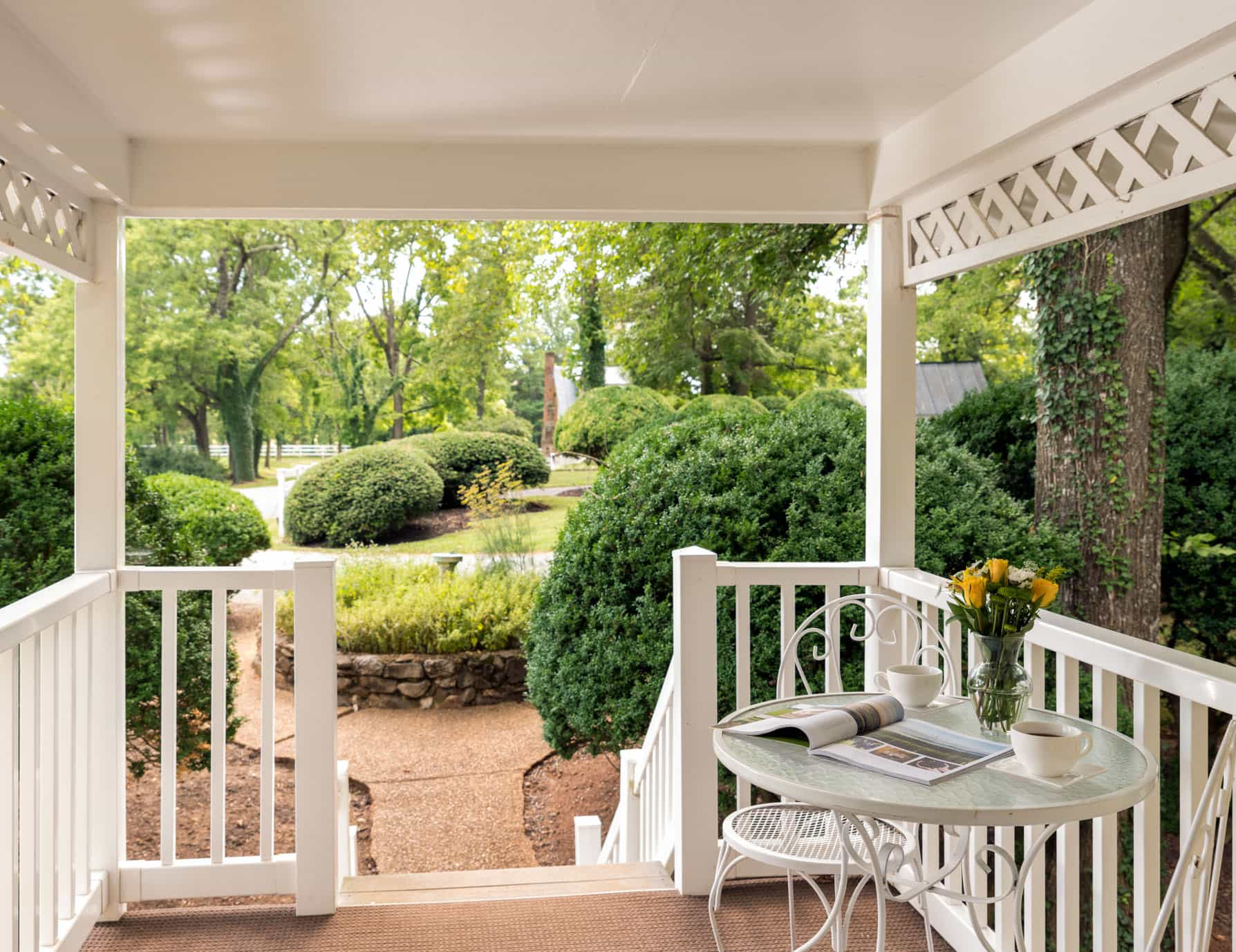 Private covered patio with a small breakfast table for two and garden views