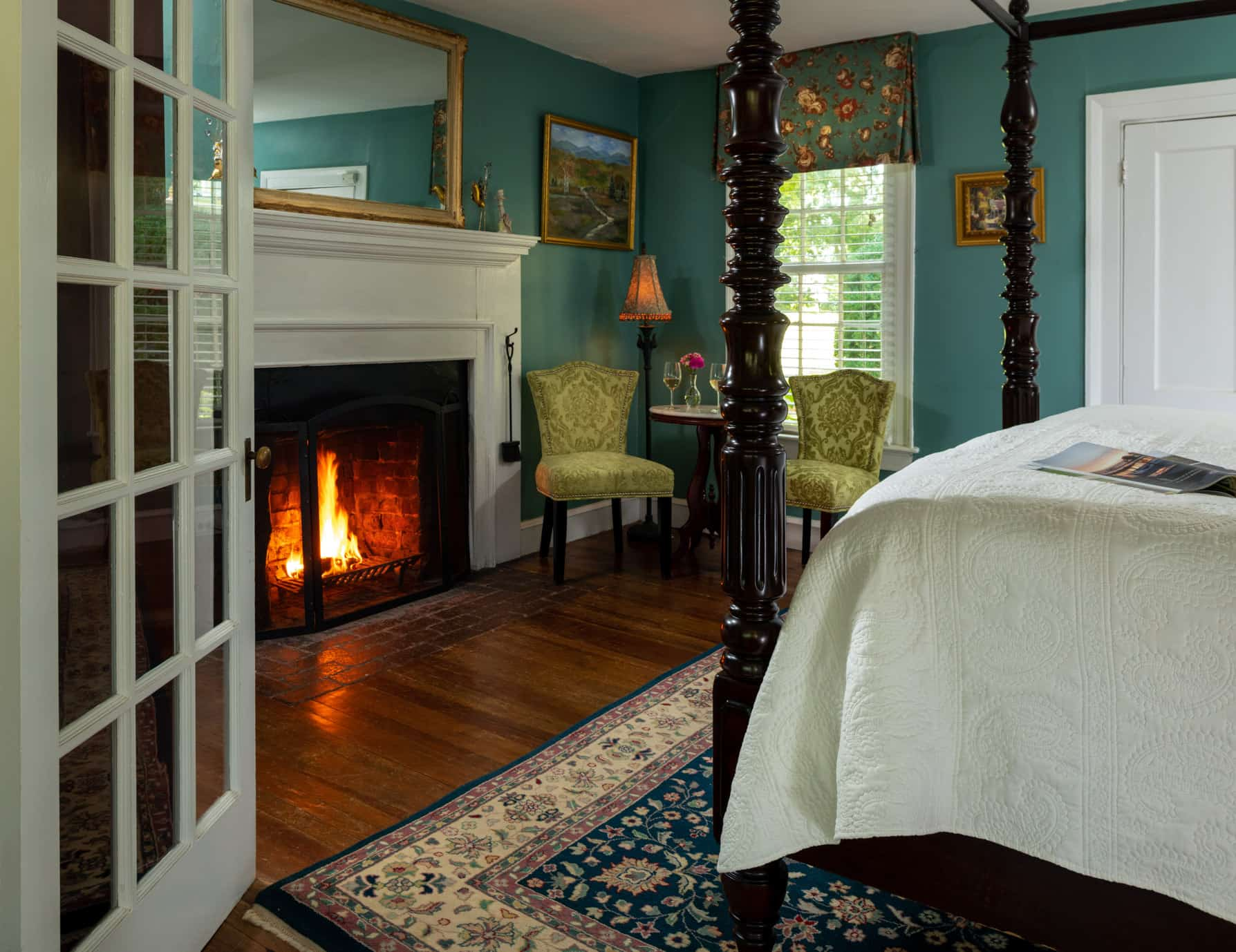 Wood-burning fireplace at the foot of a king bed