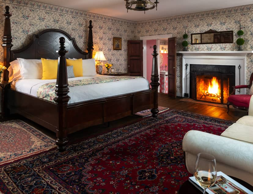 A four poster bed in a room with a fireplace