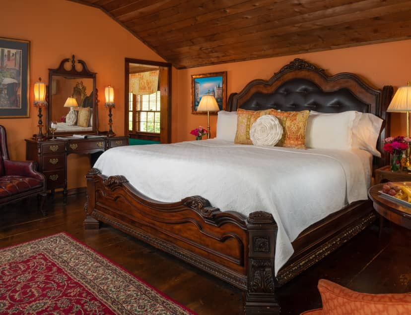 Spacious room with a king bed, tangerine walls, and wood panel ceiling