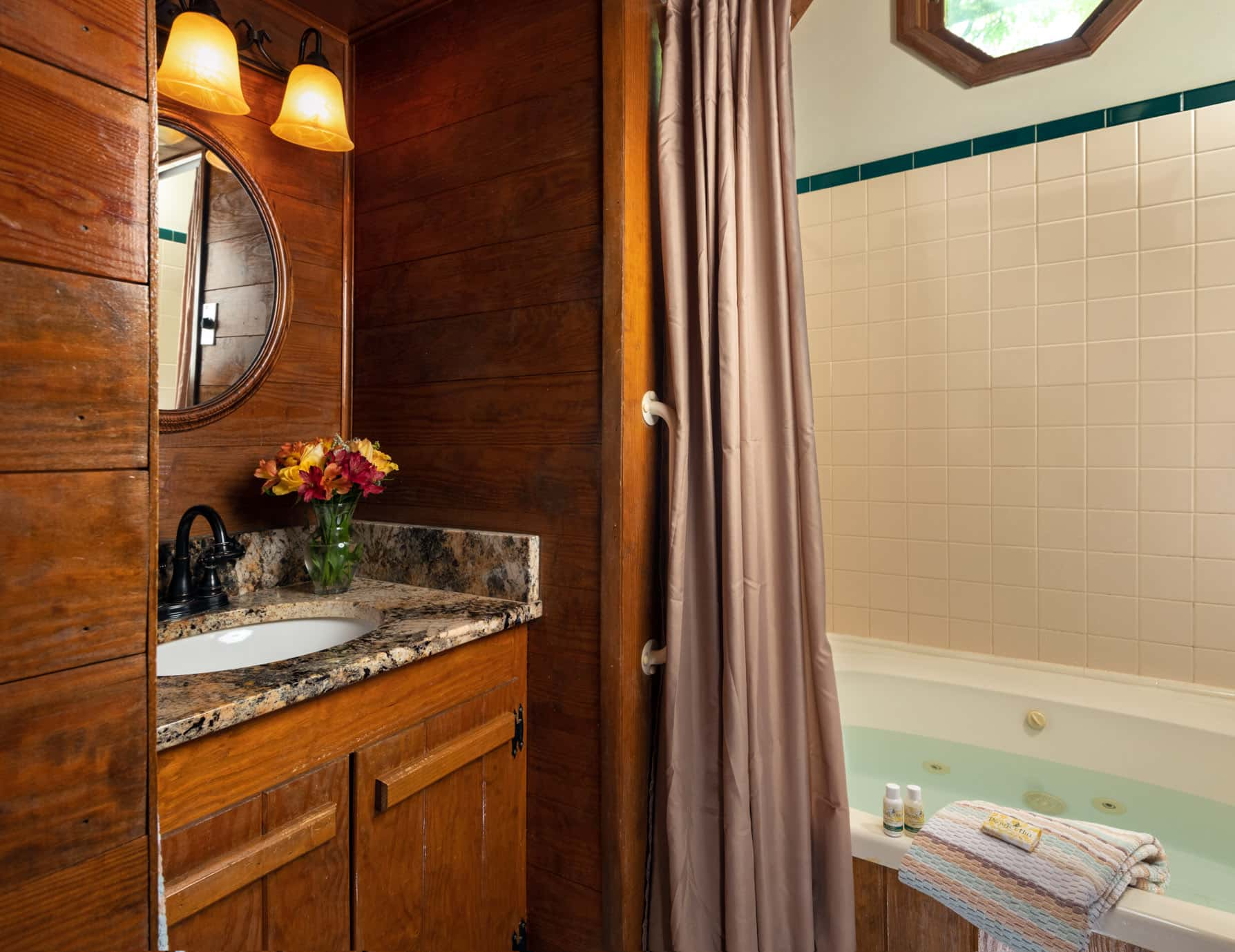 Bathroom with a jetted tub and wooden cabinets and walls