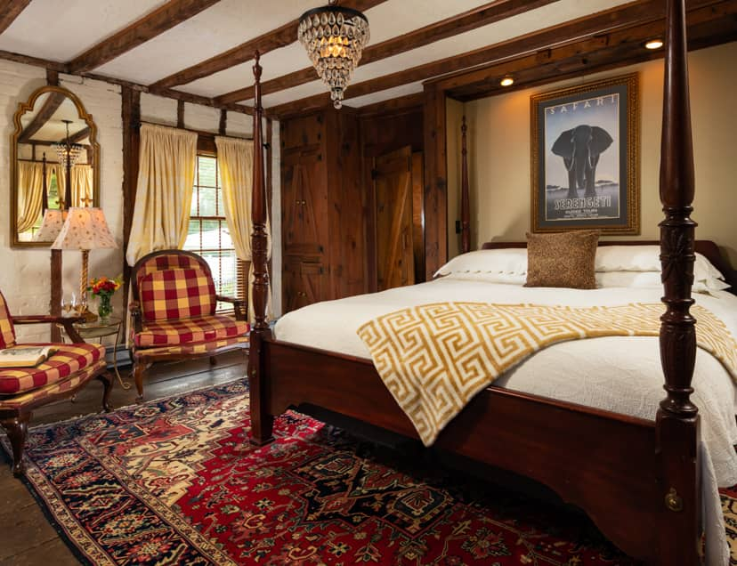 Four poster king bed in a room with exposed beams and seating area