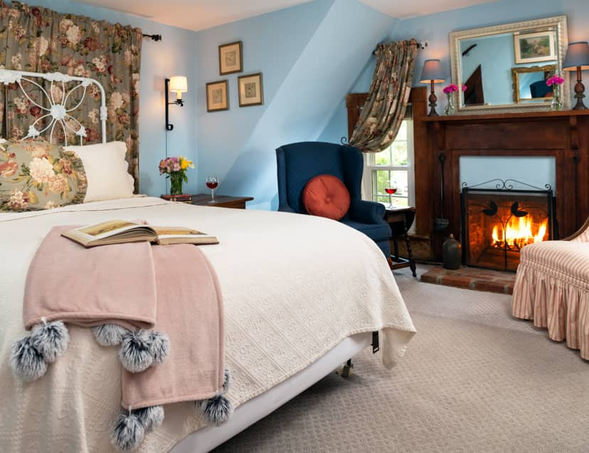 Queen bed in a cozy room with a fireplace and carpet floors