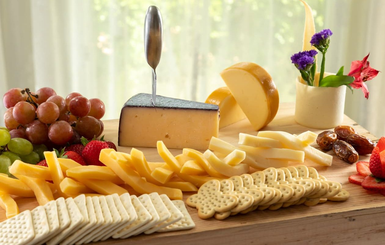 A cheese board with fruit, cheese, and crackers