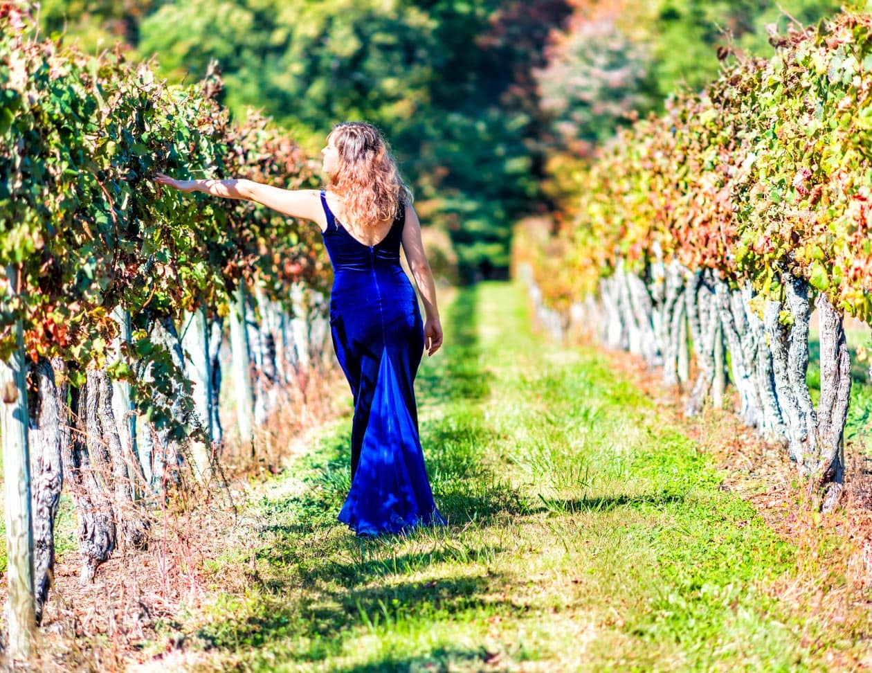 A woman in a blue dress walking in a Virginia Winery