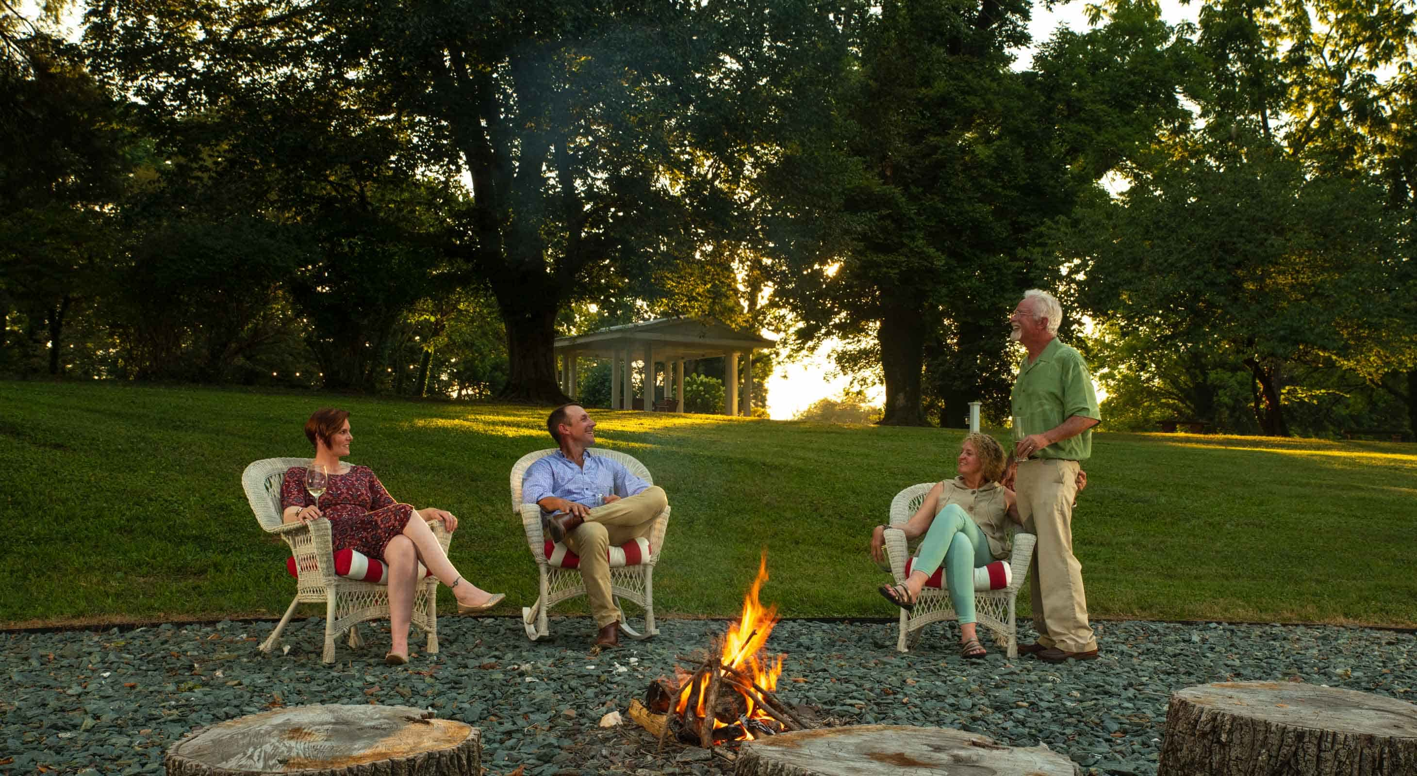 A group of people hanging out by a firepit