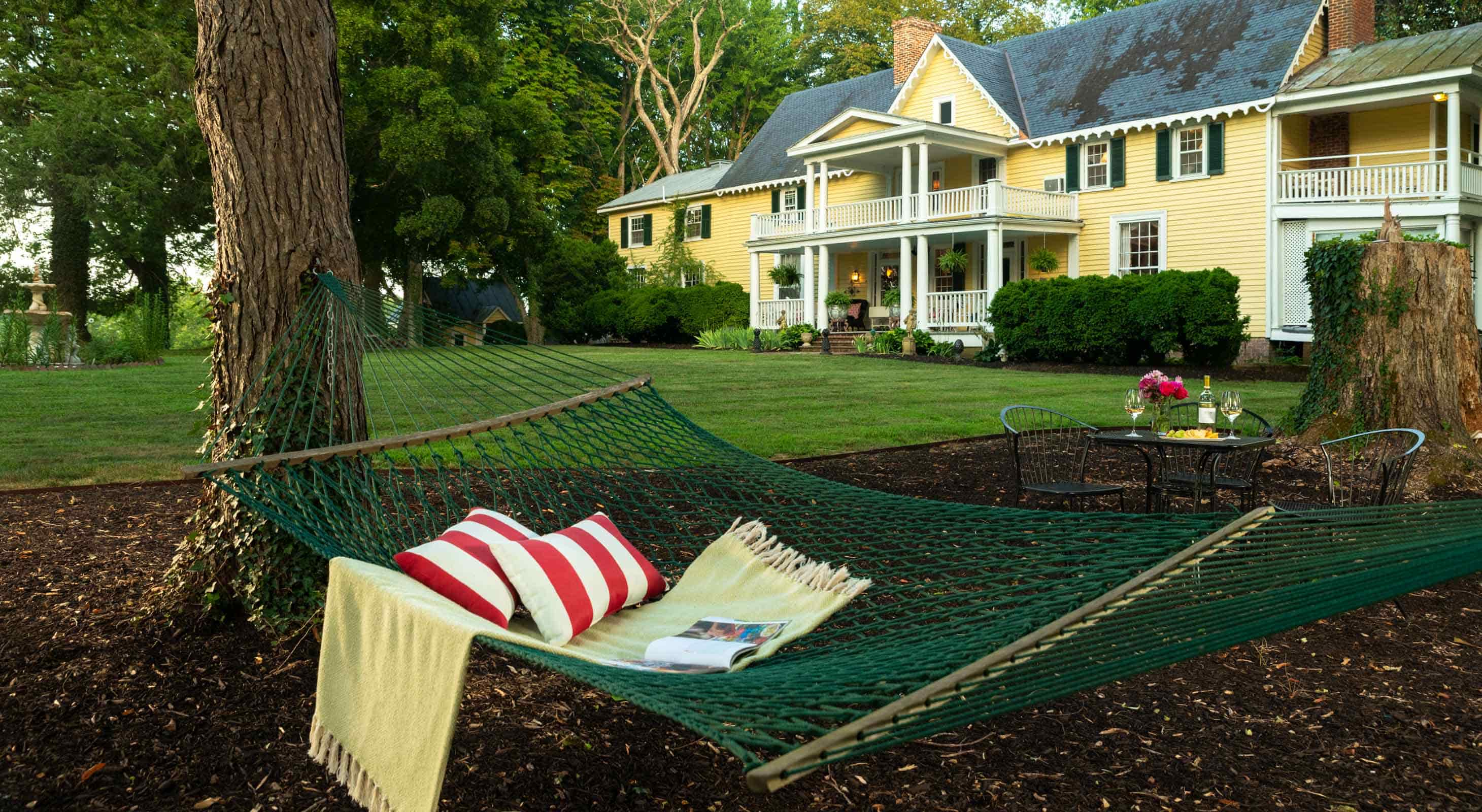 A hammock with a pillow and a book with Prospect Hill in the background