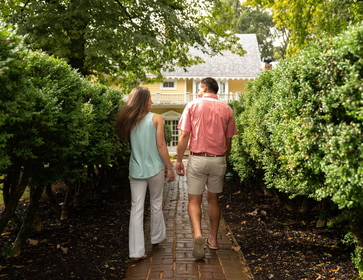 A couple walking down a brick pathway flanked by hedges