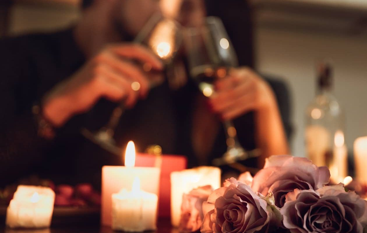 Couple drinking wine together at a table with candles and roses