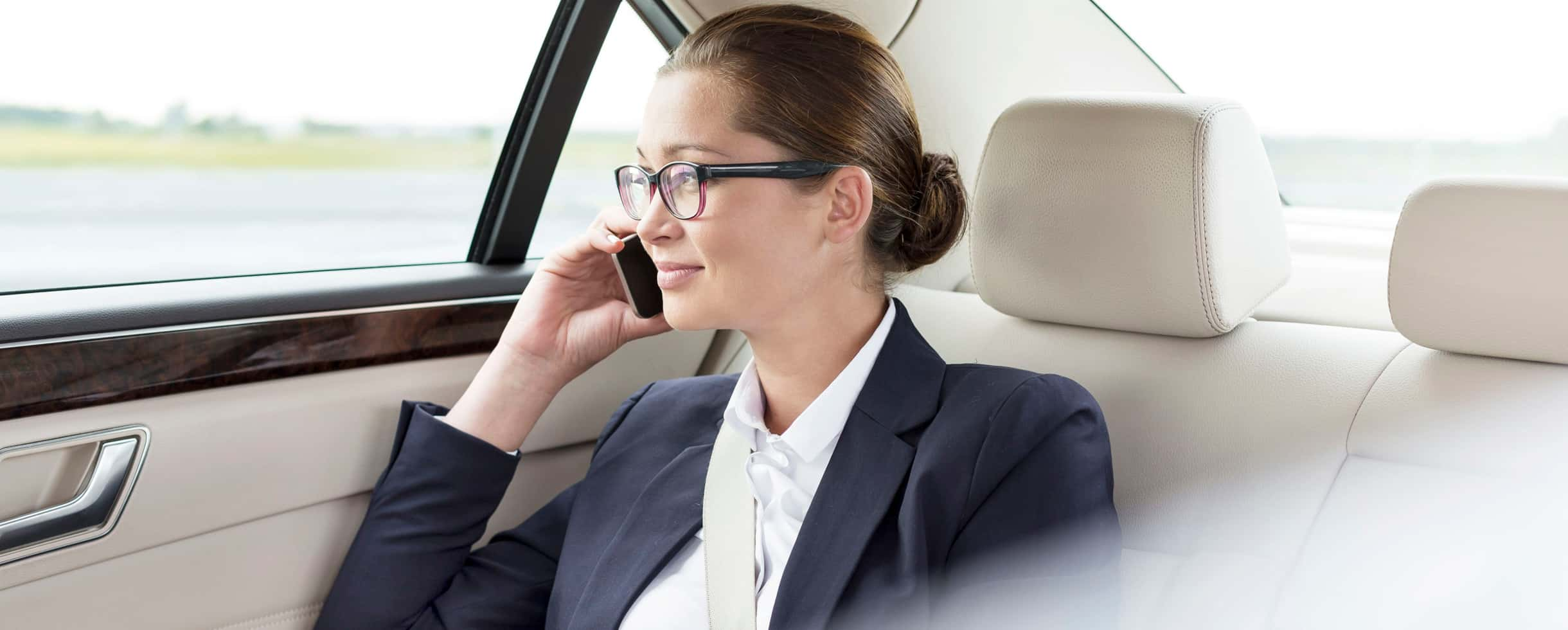 Business woman riding in the back seat of a car talking on her phone