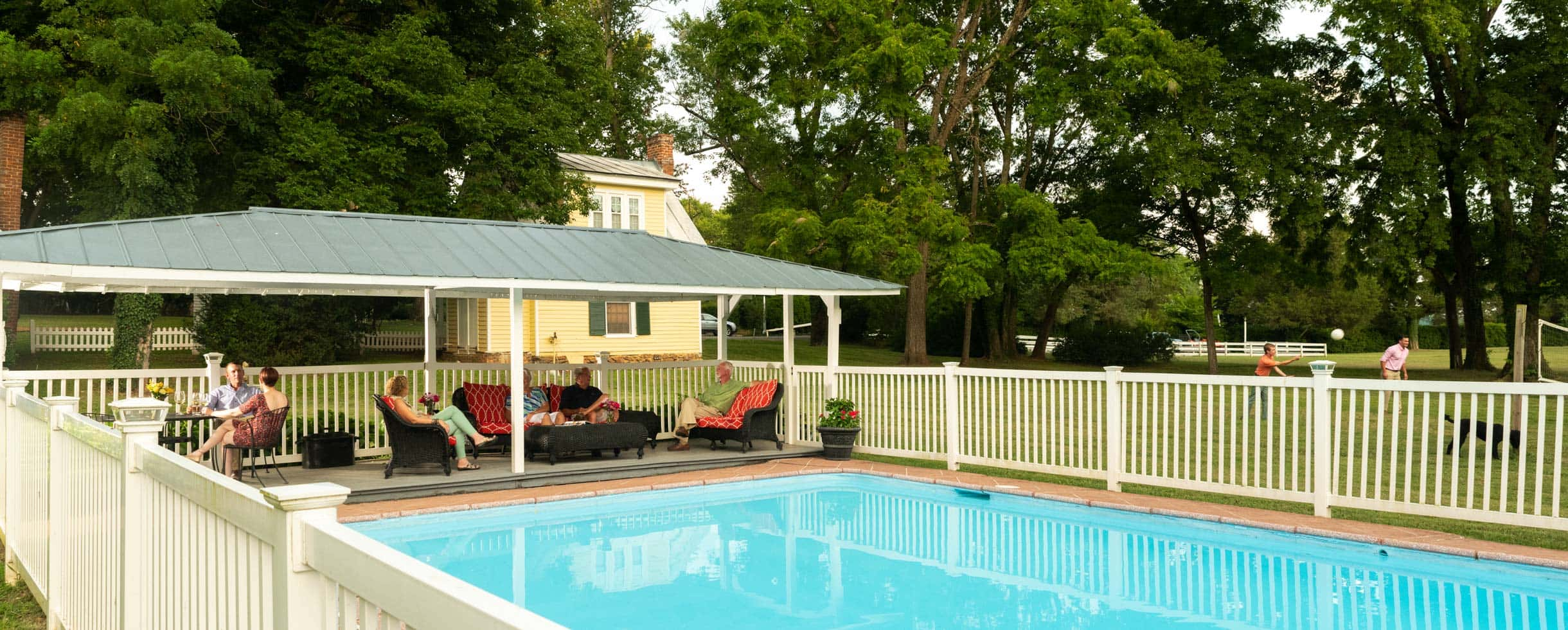 A large pool with a white fence around it, and a covered patio with deck furnature