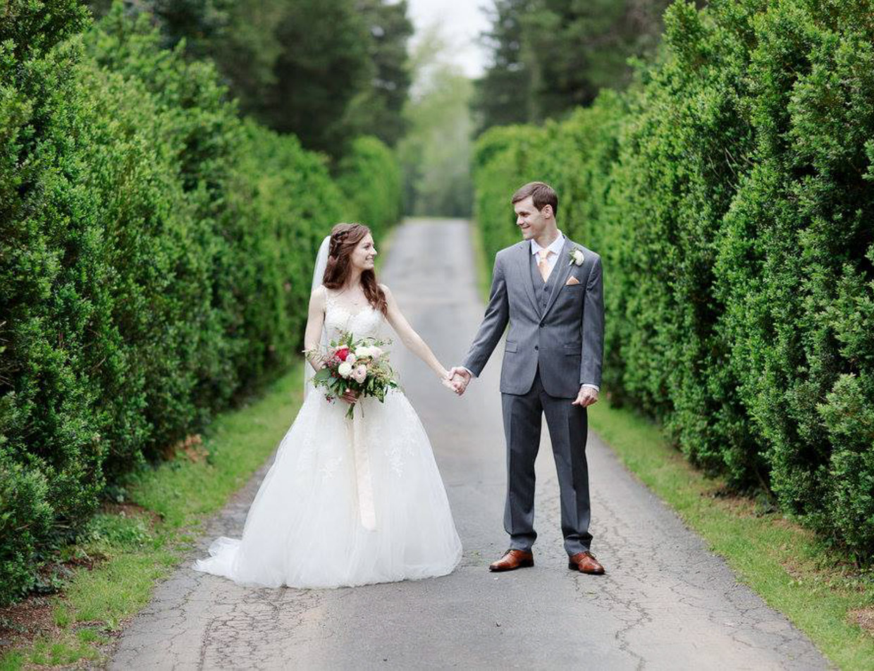 A couple holding hands, standing in a tree-lined road at Prospect Hill Inn