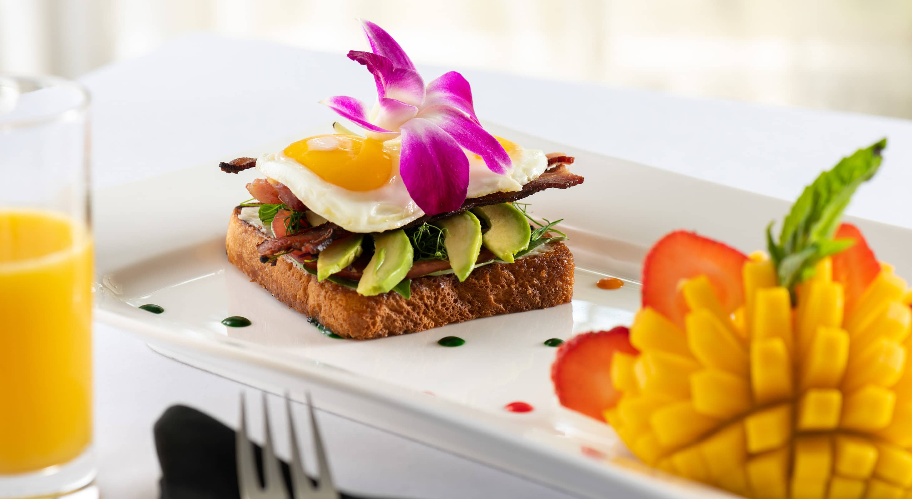Avocado toast served with mango, strawberries, and orange juice