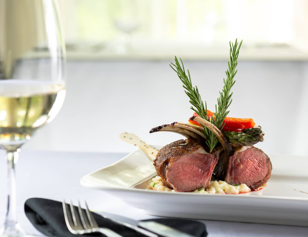 Lamb chops with two sprigs of rosemary served with a glass of white wine