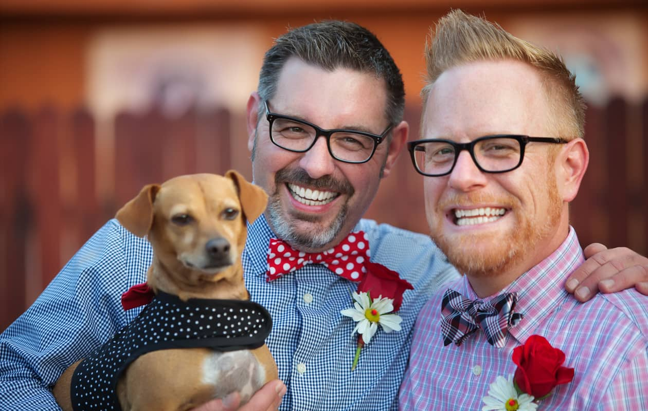Gay couple wearing bowties holding a small dog