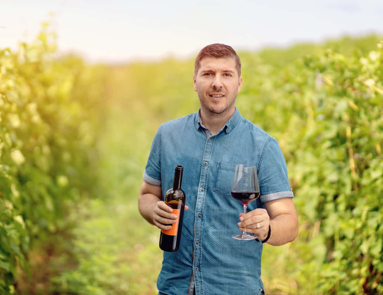 Man holding a bottle of wine in a vineyard
