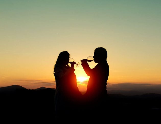 couple drinking wing with sun setting in background