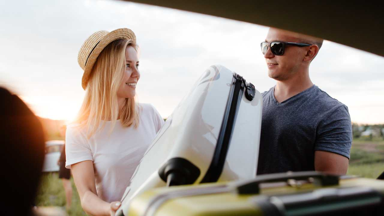 Young couple loading white suitcase in automobile.